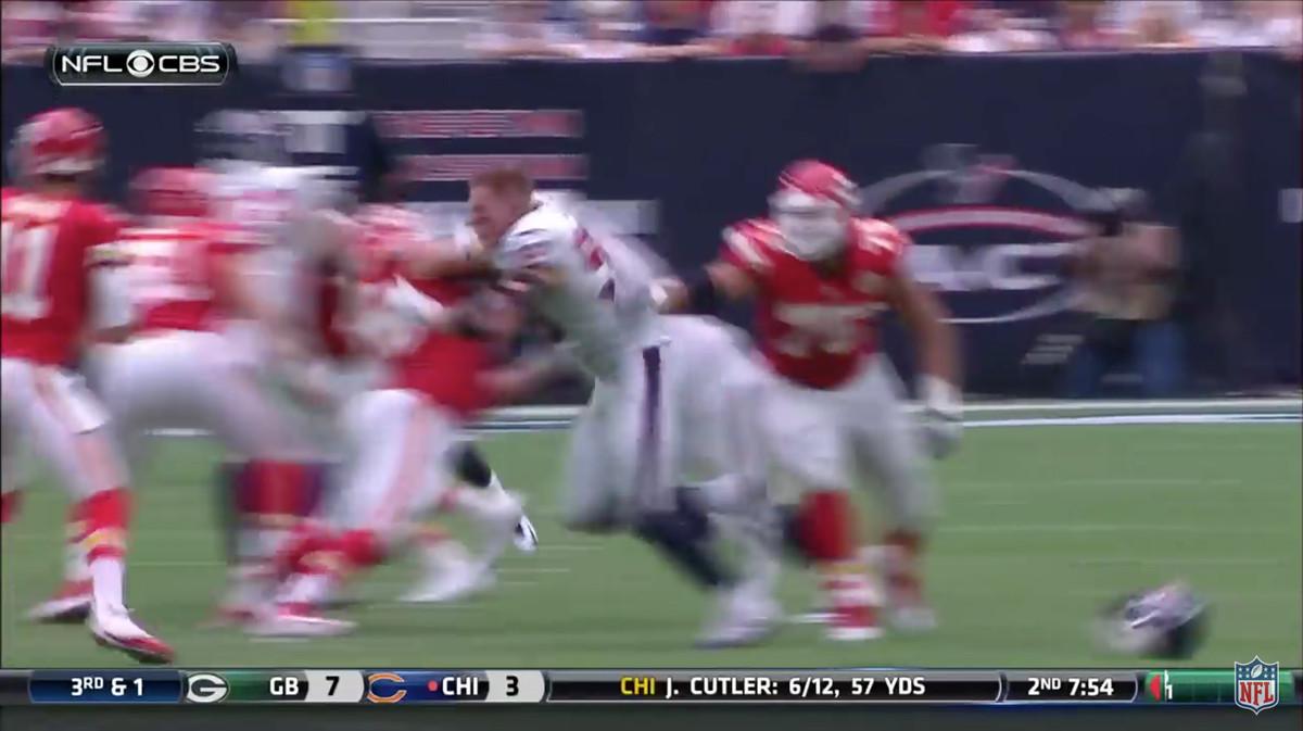J.J. Watt sacking the quarterback without his helmet