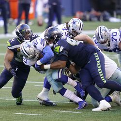 Seattle Seahawks middle linebacker Bobby Wagner, left, and defensive tackle Bryan Mone (92) tackle Dallas Cowboys running back Ezekiel Elliott (21) during the second half of an NFL football game, Sunday, Sept. 27, 2020, in Seattle. The Seahawks won 38-31.