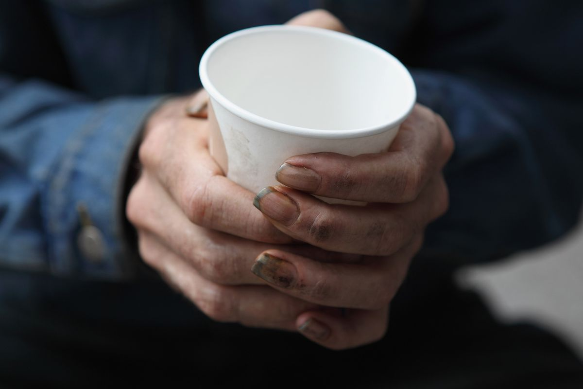 A homeless man holds a cup as he begs panhandles for spare change on September 16, 2010 in San Francisco, California.