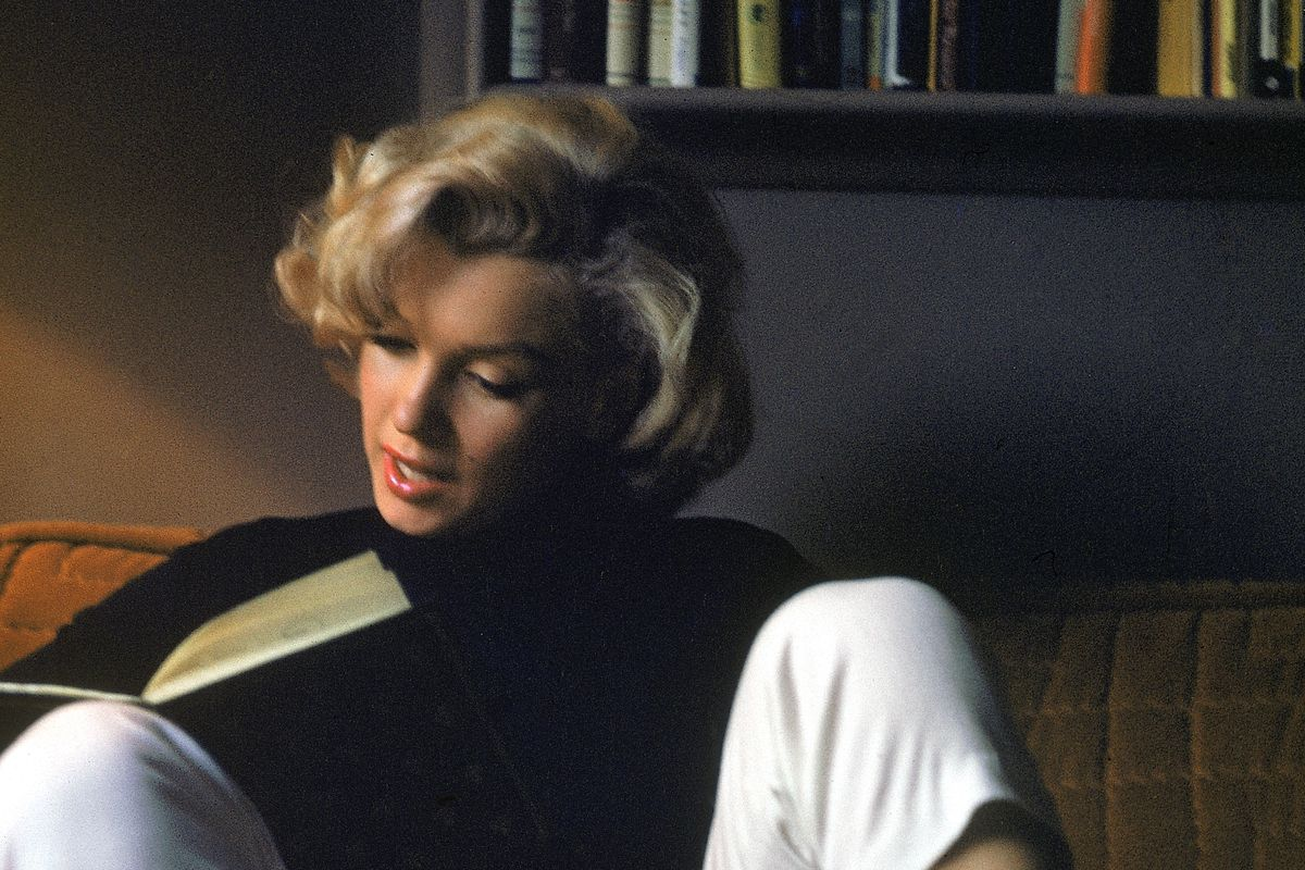 Marilyn Monroe reading at home.