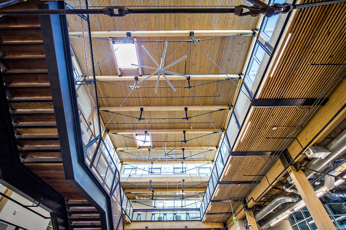 An interior of an airy building with giant fans way above.