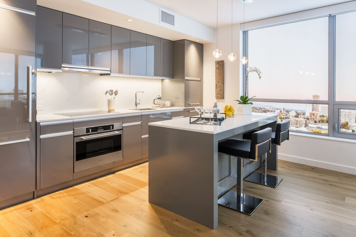 A kitchen in an open floor plan full of gray cabinets
