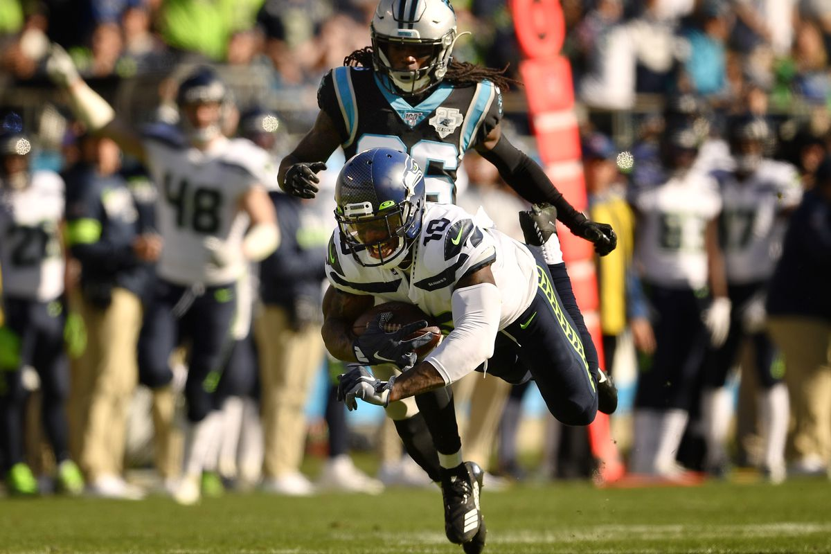 Seattle Seahawks wide receiver Josh Gordon #10 runs the ball as Carolina Panthers cornerback Donte Jackson #26 tries to defend in the game at Bank of America Stadium on December 15, 2019 in Charlotte, North Carolina.