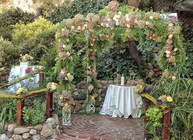 A floral-covered patio at Inn of the Seventh Ray. There is a table with a white tablecloth on the patio. There is a lectern right outside of the patio.
