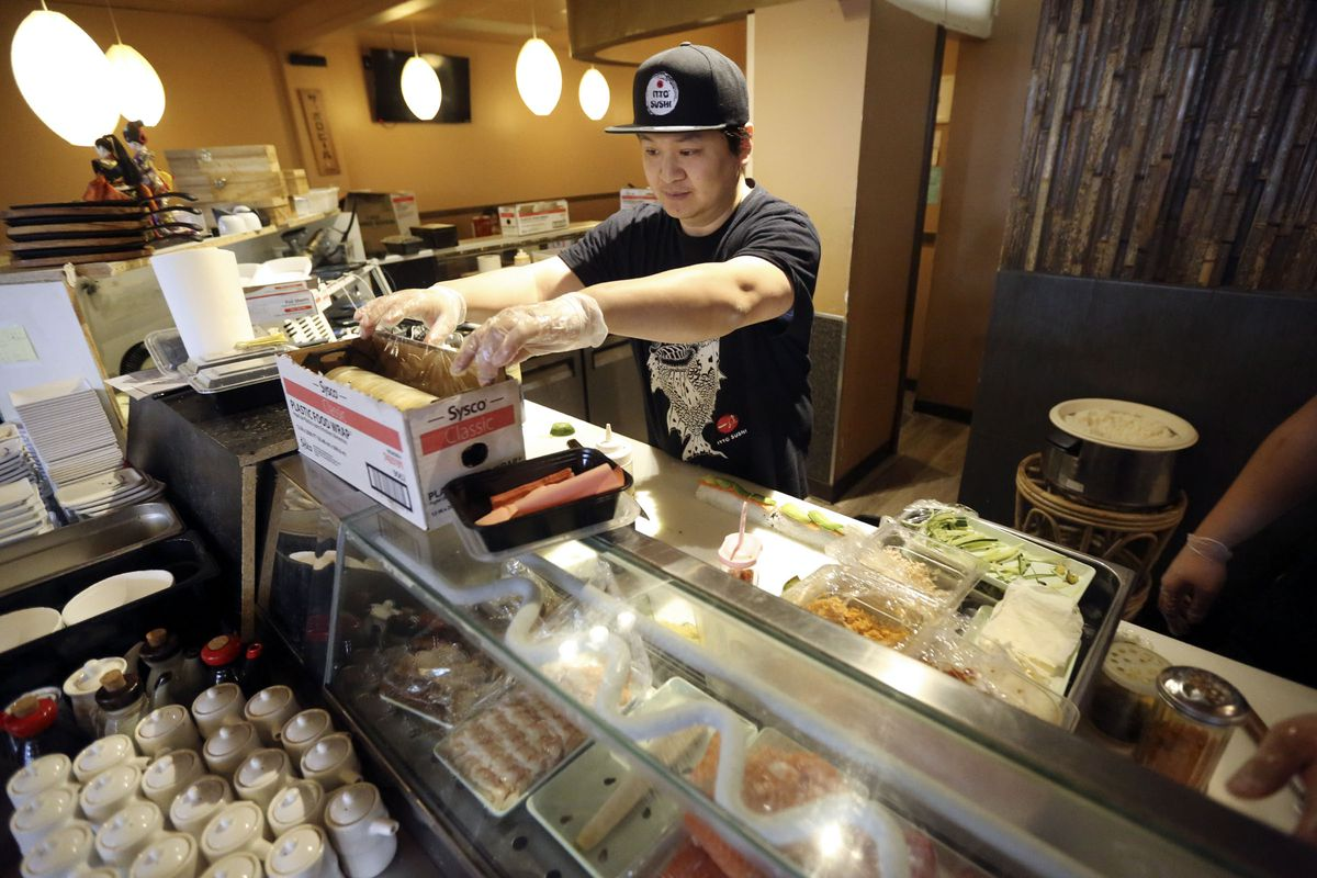 Yong Itto, owner of Itto Sushi in Midvale, prepares sushi for a to-go order on Wednesday, March 25, 2020. Small businesses are struggling with a loss of business during the COVID-19 pandemic. Customers are not allowed to dine in at restaurants.