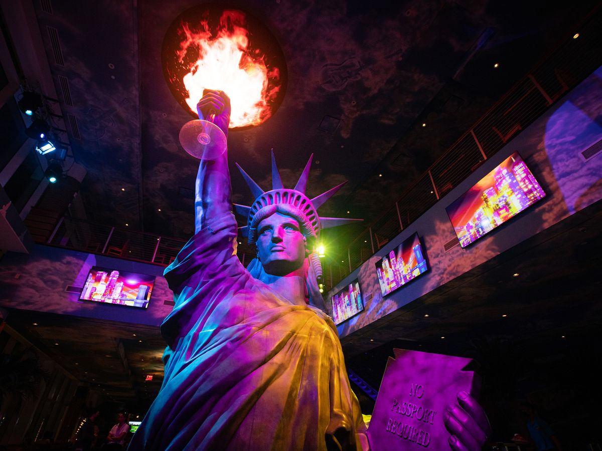 A statue of liberty holds a giant margarita that is projecting flames.