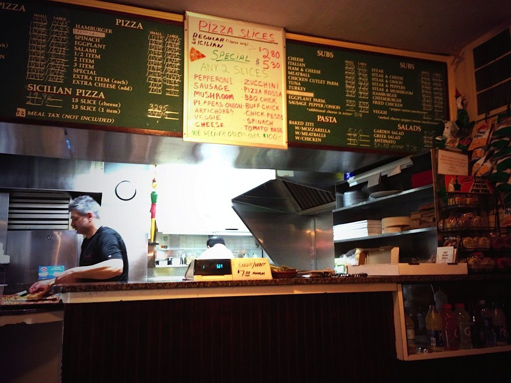 The menu board, counter, and an employee at Pinocchio's in Harvard Square