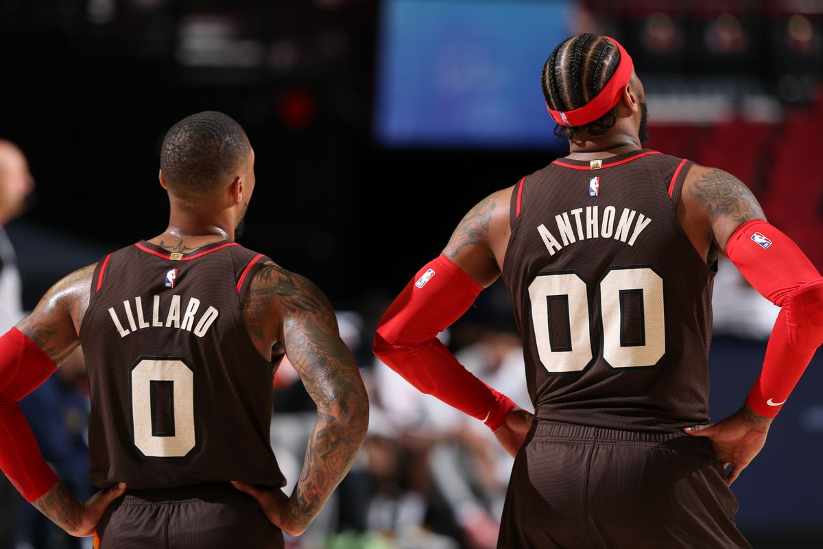 Damian Lillard #0 and Carmelo Anthony #00 of the Portland Trail Blazers looks on during the game against the Denver Nuggets on May 16, 2021 at the Moda Center Arena in Portland, Oregon