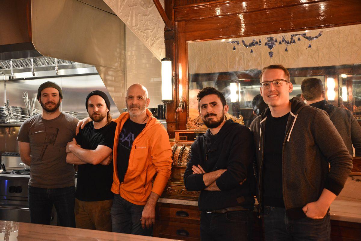 five men standing in front of mirror in restaurant
