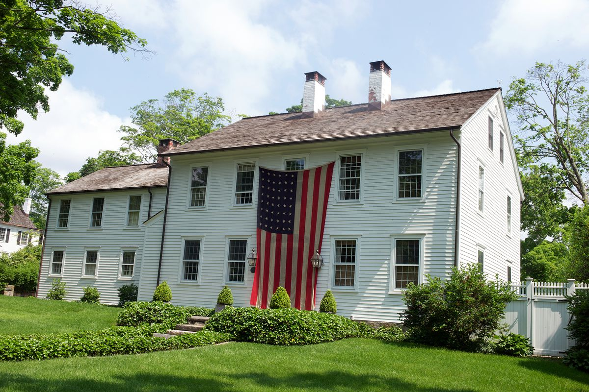 A house with a two-story-size American flag on the front.