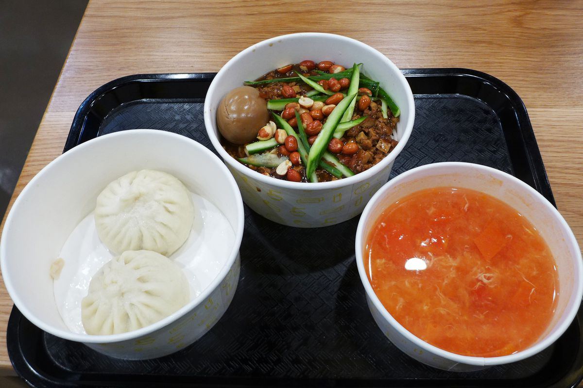Three paper carryout containers feature a pair of puffy buns, a noodle dish topped with peanuts, and a thin red soup...