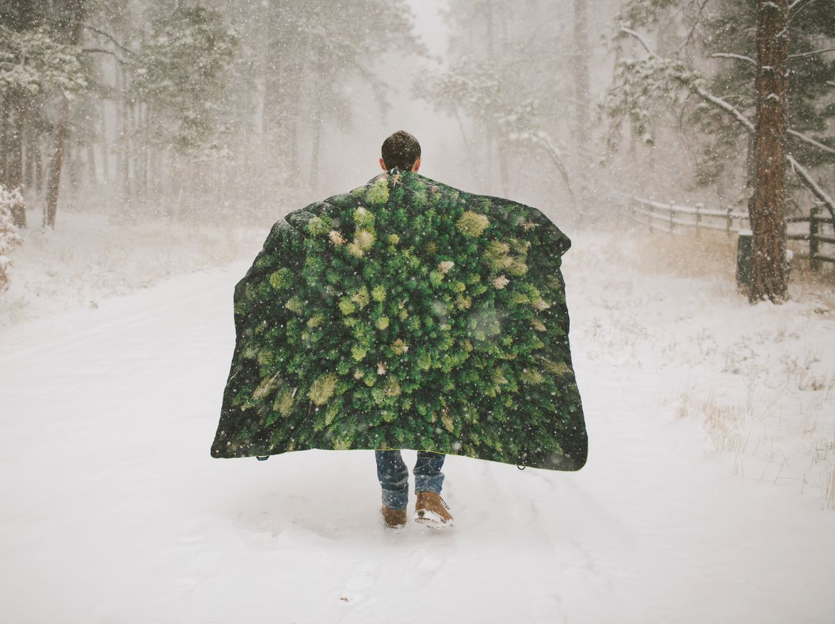 A person walks along a snow covered path with a blanket draped over their shoulders. The blanket has a picture of the tops of trees on it.