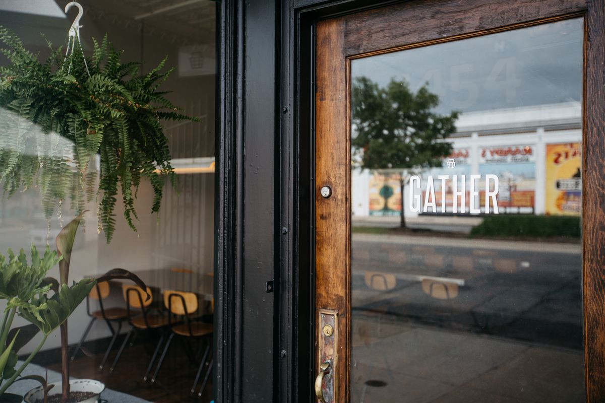 The glass door at the entrance to Gather looks in on a dining room with communal seating and schoolhouse chairs.