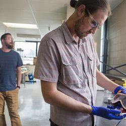 Recent University of Utah graduate Tom Folke, left, and Simone Longo work on a pair of prototype goggles in the Chemical and Mechanical Engineering Building on the U. campus in Salt Lake City on Thursday, June 1, 2017. The googles employ new technology that allows them to dim electrochemically.