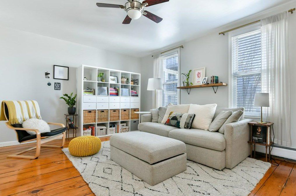 A living room with a couch and some shelves next to the couch.