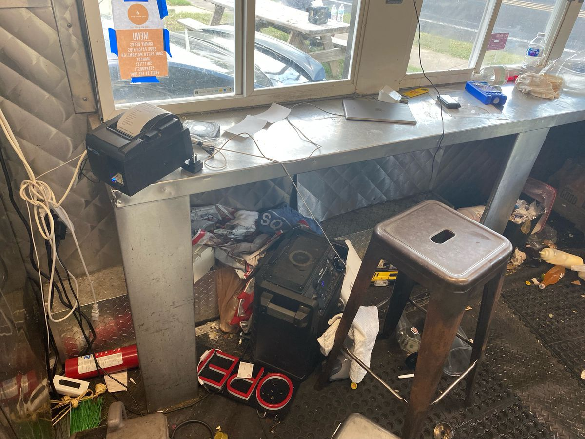 The inside of a food truck counter window area with a mess of items everywhere
