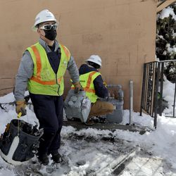 Dominion Energy utility workers Ramone Barrera and Kylie Hrubes replace a gas meter in West Valley City on Wednesday, Feb. 17, 2021.