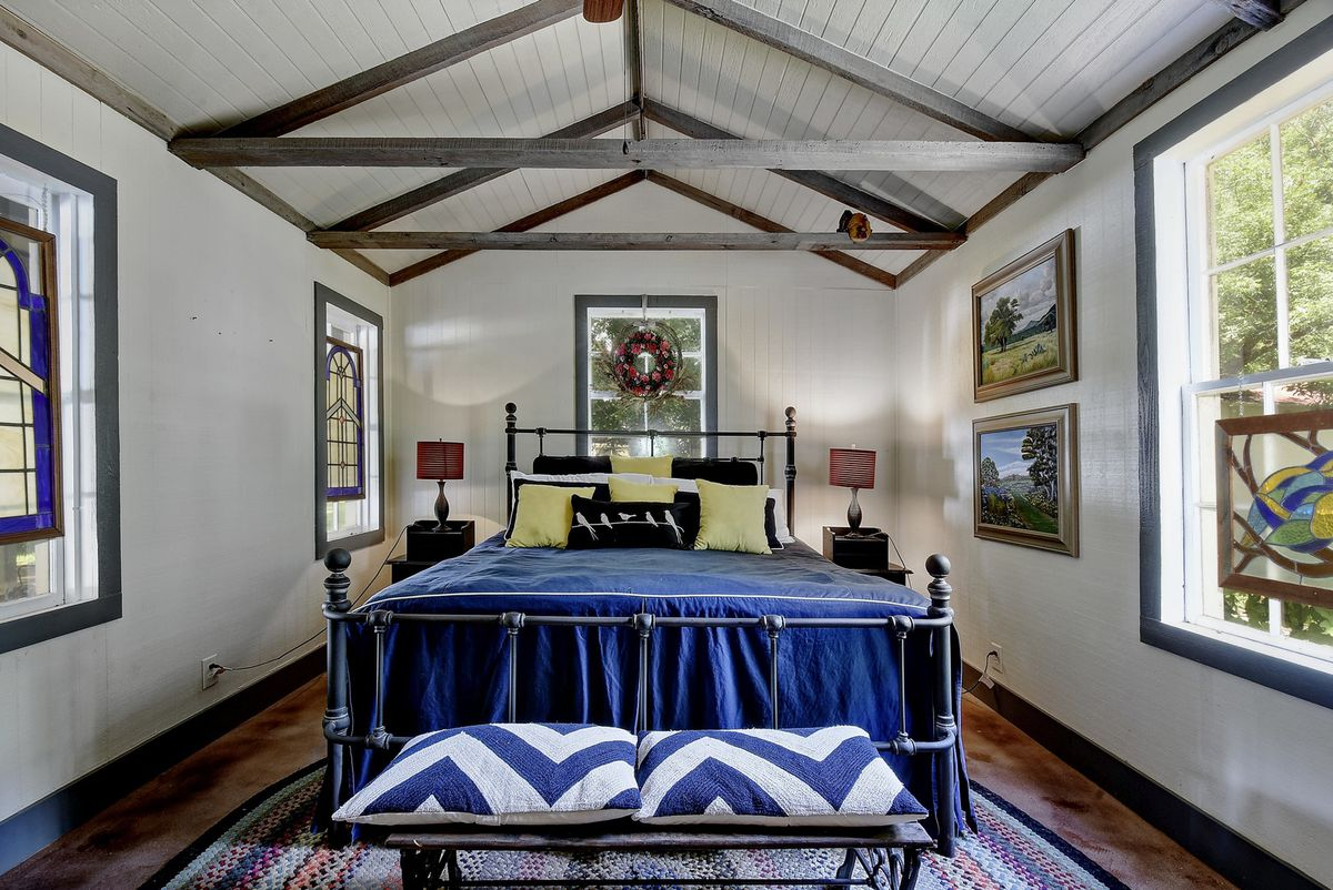 A bedroom features a blue bed on steel frame with wooden floors and lots of windows.