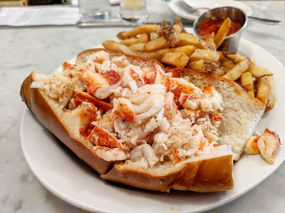 A lobster roll with a side of fries and ketchup sits on a white plate on a marble bar