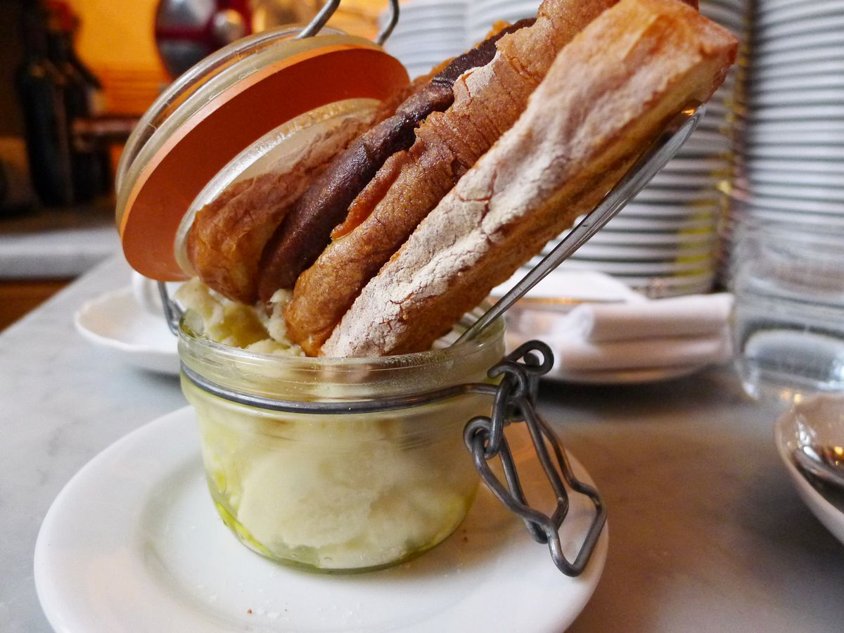 A jar with white food inside it and slices of baguette stuffed in the top.