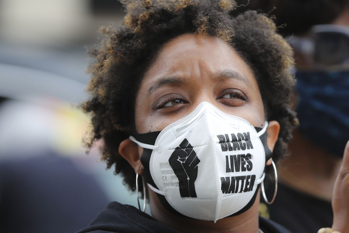 "A Black person wearing a face mask that reads ""Black lives matter."""