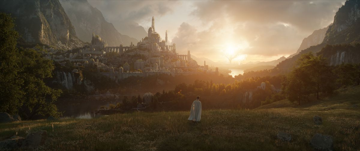 a woman in a white cape stands on a grassy ridge overlooking an elven city in Amazon Studios' untitled Lord of the Rings TV series