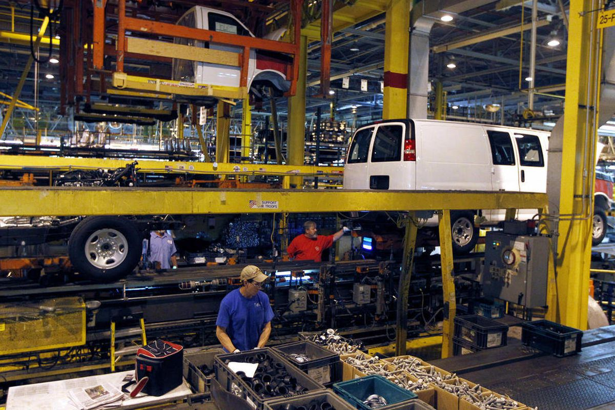 FILE - In this Nov. 3, 2011, file photo, General Motors employees work on a van assembly line at GM's plant in Wentzville, Mo. The U.S. auto industry, already stretched to meet growing car and truck sales, faces parts shortages that could limit the number
