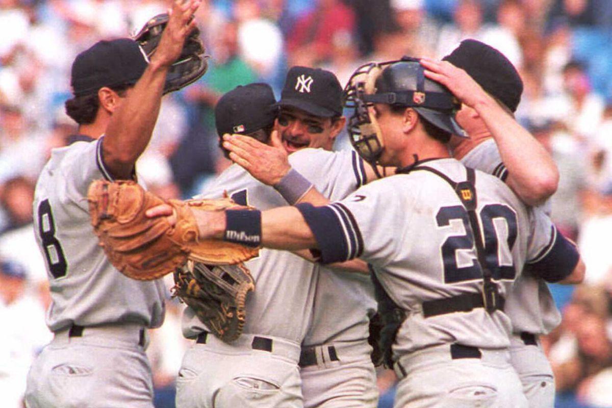 Don Mattingly of the New York Yankees (C) hugs tea