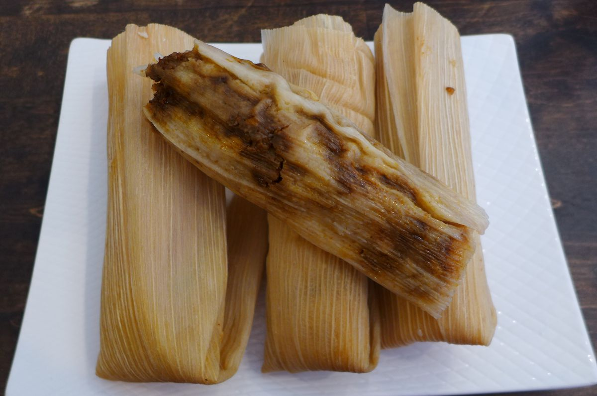 An assortment of tamales from Factory Tamal, chicken mole on top