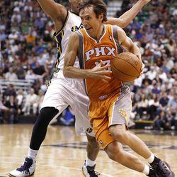 Phoenix Suns guard Steve Nash (13) drives past Utah Jazz guard Devin Harris (5) during the first half of an NBA basketball game, Tuesday, April 24, 2012, in Salt Lake City. (AP Photo/Jim Urquhart)