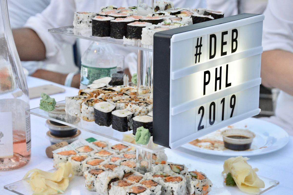 a tiered plate of sushi and a sign that says deb phl 2019