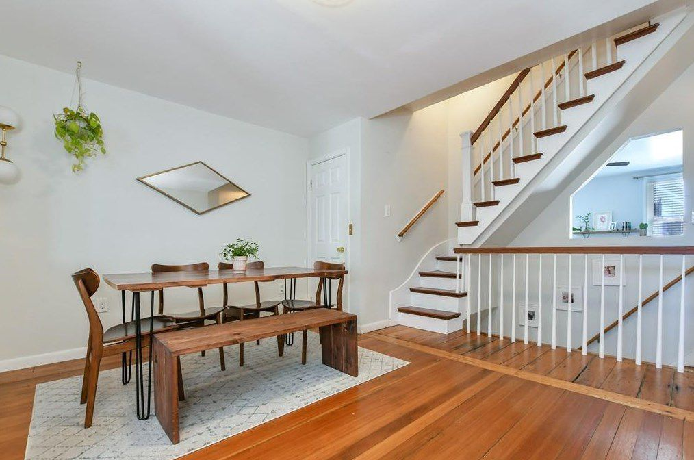 A roof with a table and chairs just off a stairway landing.