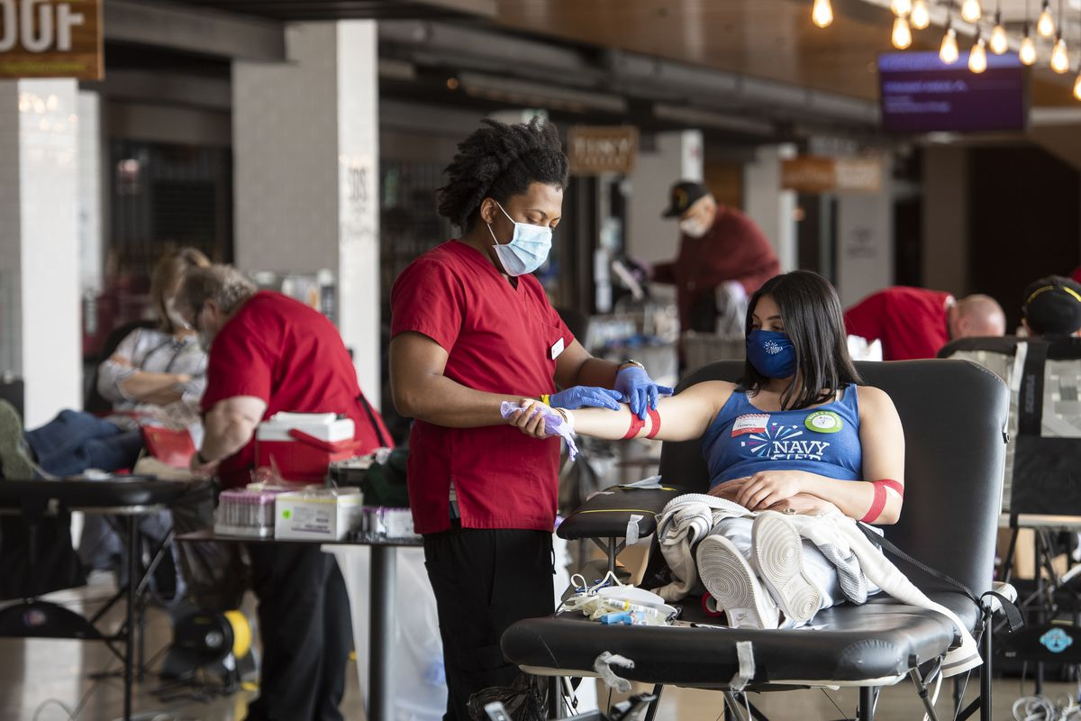 A Red Cross phlebotomist ties a woman's arm with medical tape after she gave blood, at a Red Cross blood drive at Navy Pier, Monday, May 4, 2020. | Tyler LaRiviere/Sun-Times