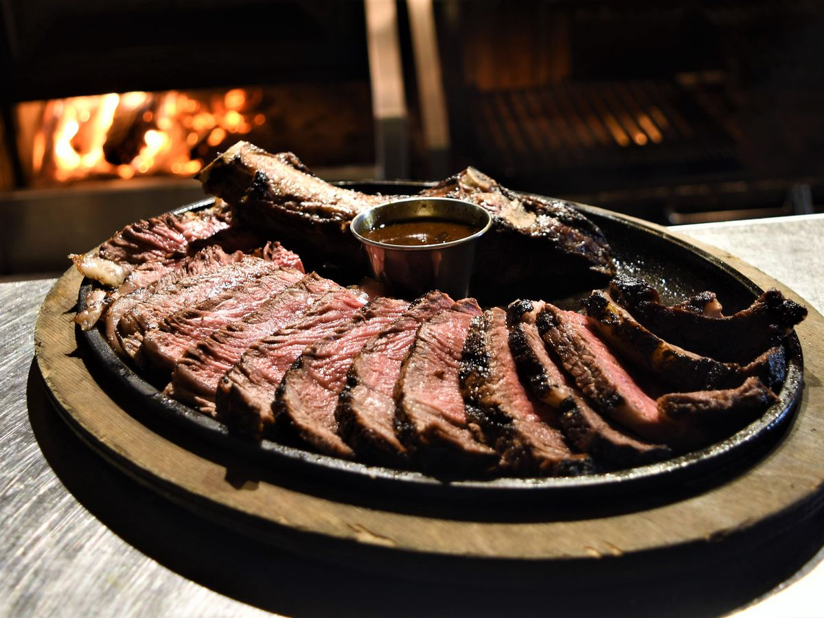 A dozen slices of steak arranged around the bone in a circular plate on a white table