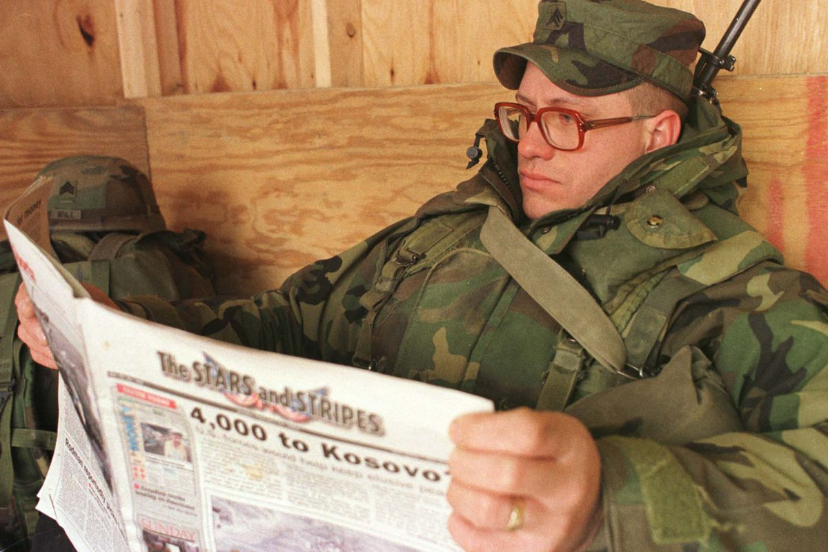 """A soldier wearing red glasses, and a heavy camouflage coat, looks serious, reading a Stars and Stripes paper with the main headline """"4,000 to Kosovo."""""""