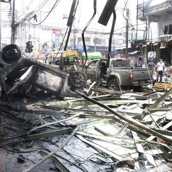 Wreckage of cars lie on the road after car bombs blasted in Yala province, Southern Thailand Saturday, March 31, 2012. Suspected Muslim insurgents set off coordinated bomb blasts as shoppers gathered for lunch Saturday in a busy hub of Thailand's restive south.