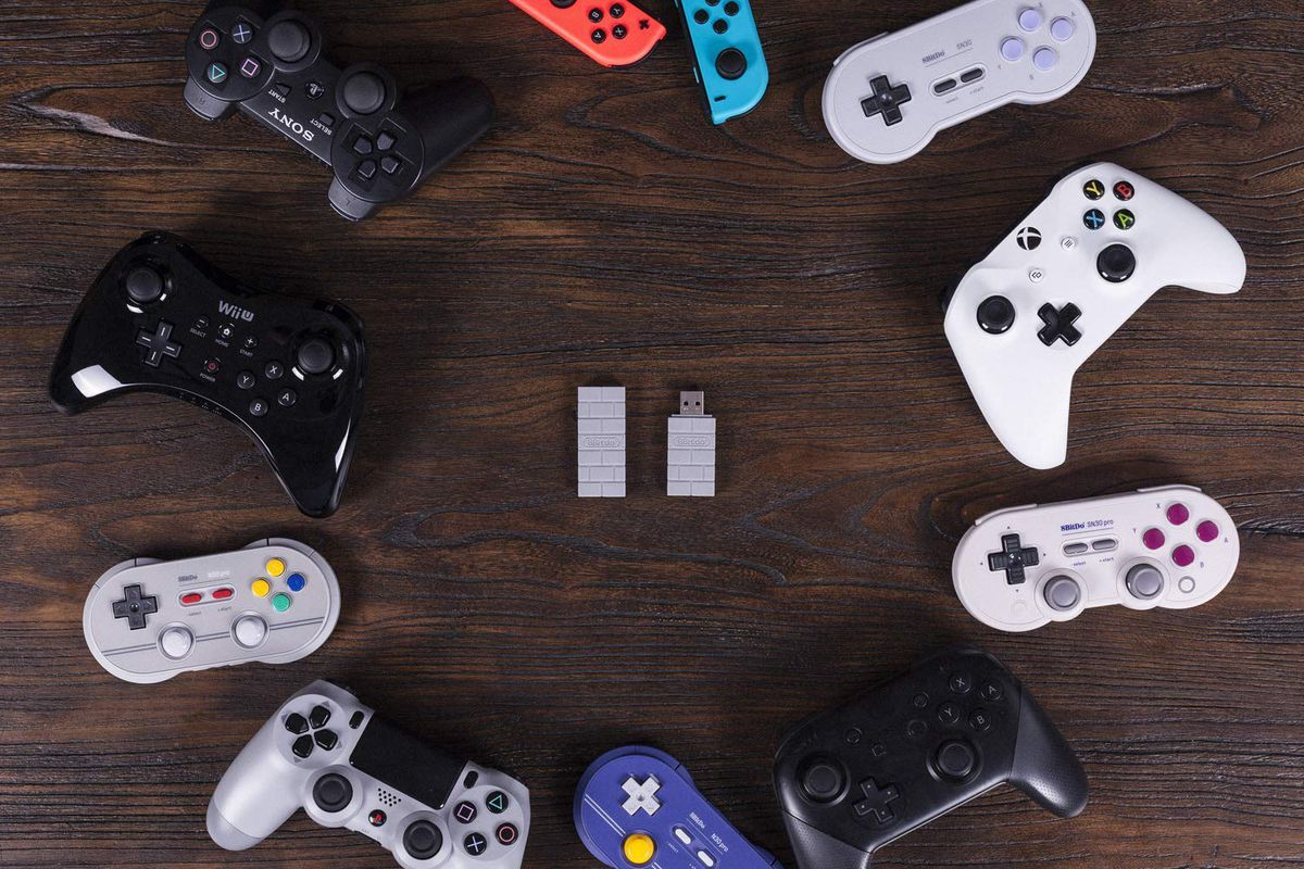 an 8BitDo wireless adapter surrounded by controllers