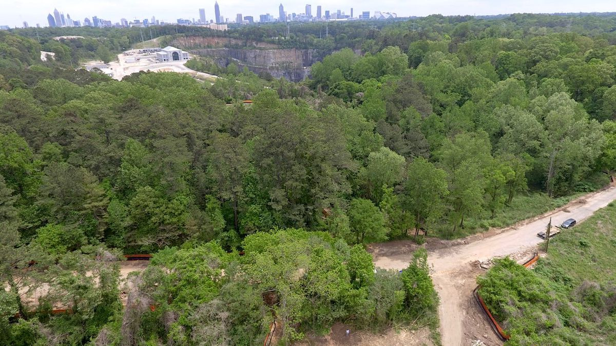 A lush forest is dissected by a dirt trail. A vast quarry and the beginnings of new construction are visible in the background.
