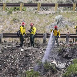 Fire crews work to put out a brush fire on the eastbound side of Interstate 70 on Wednesday, June 28, 2017, in Avon, Colo. The Vail Valley is under a Red Flag Warning due to hot temperatures and gusty winds.
