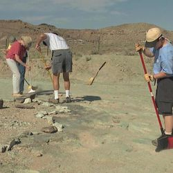 Volunteers sweep debris that has a new collection of dinosaur footprints from view in Moab.