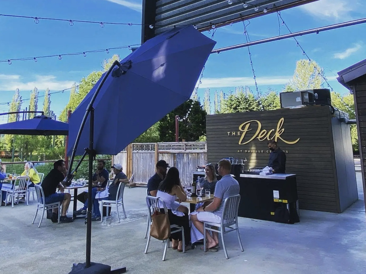 The Deck at DeLille Cellars with customers sitting at tables under blue umbrellas and the space's name behind a host station.