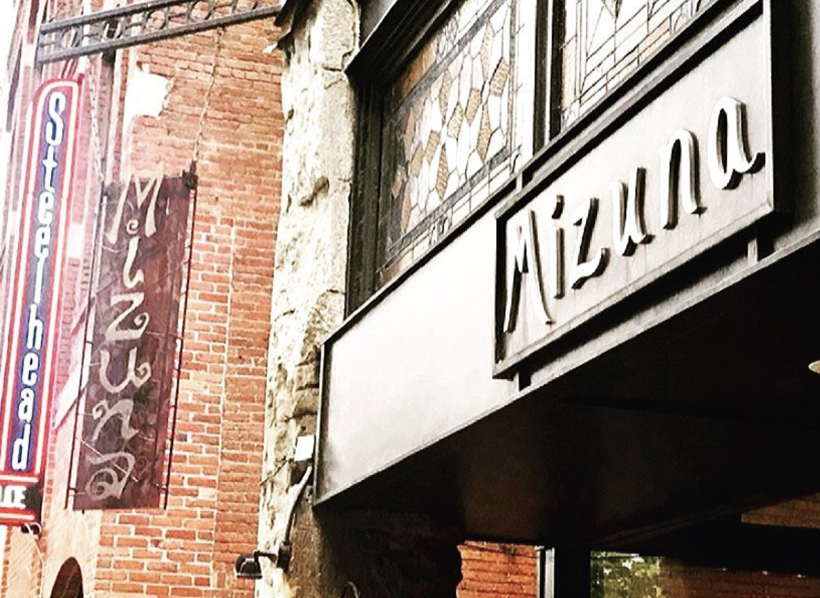 The outside of Mizuna Restaurant in Spokane, with the restaurant's name on the front and on a nearby brick wall