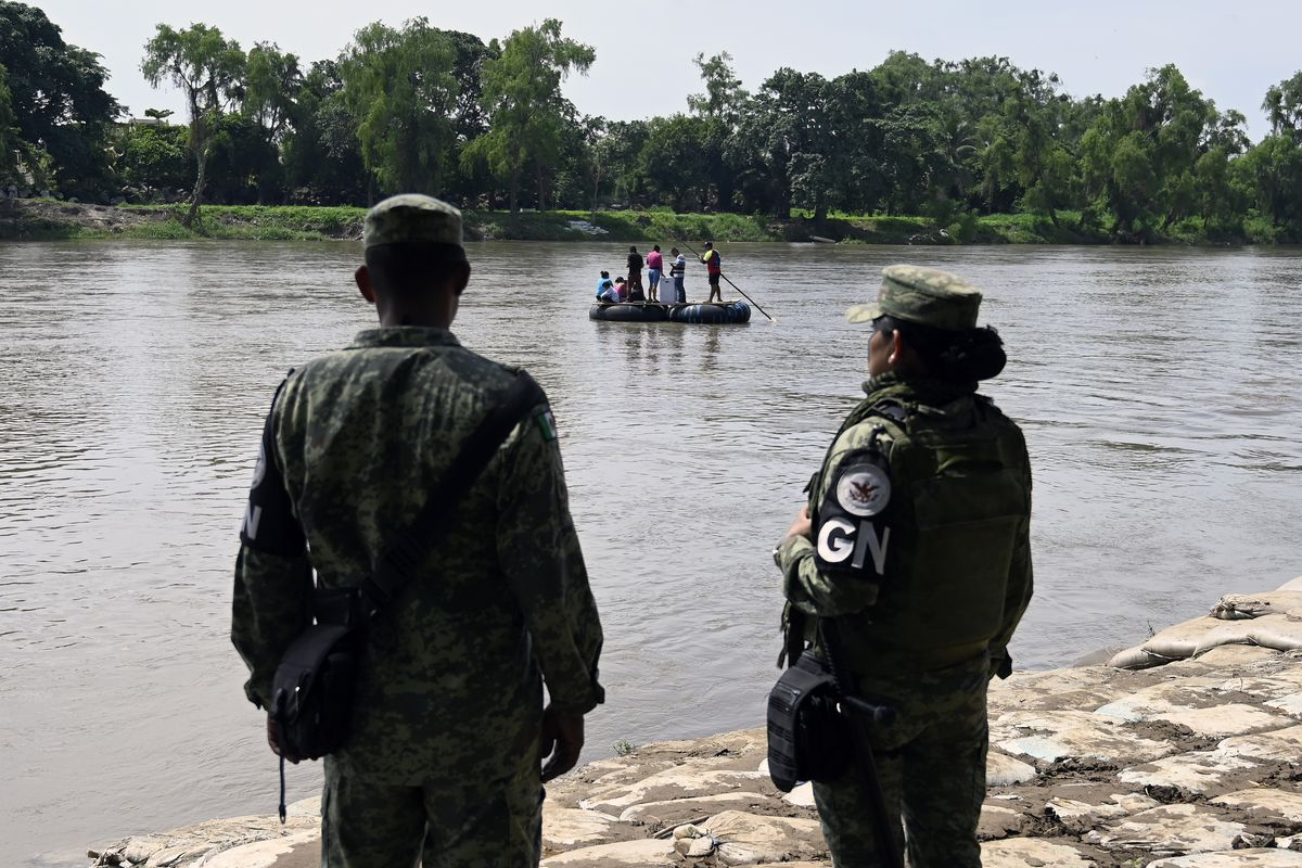 Two Mexican National Guardspeople stand at the banks of the Suchiate river, watching a raft fashioned from scrap rubber carrying several people.