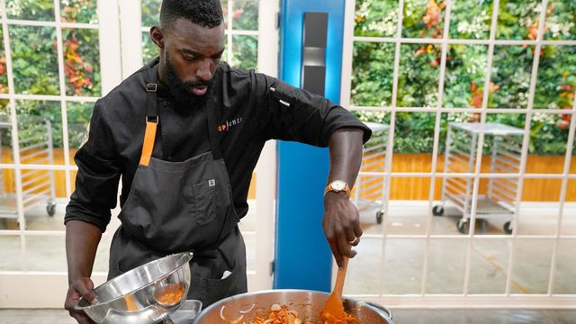 Top Chef all-star contestant Eric Adjepong focuses intensely on stirring a bright orange dish on a stovetop.