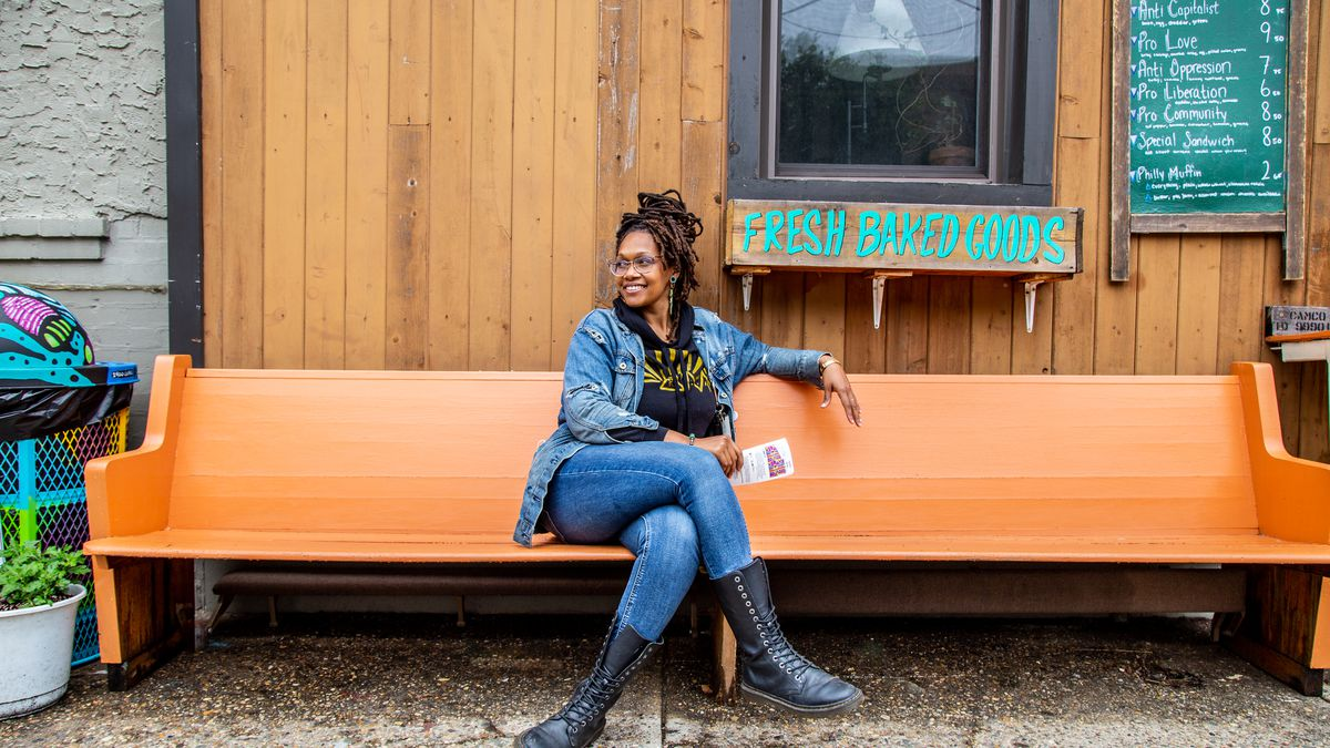 Founder of Franny Lou's Porch, Blew King, sits cross-legged in jeans and black boots on an orange bench at a coffee shop