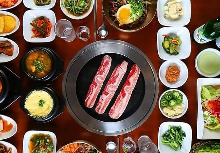 A buffet of Korean dishes with pork belly in the middle, ready to be cooked.