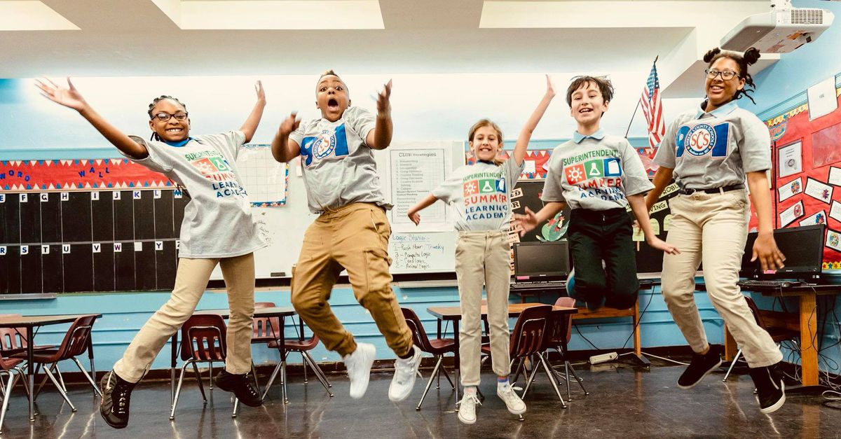 Students in Summer Learning Academy logo shirts jump in a classroom for the photo.