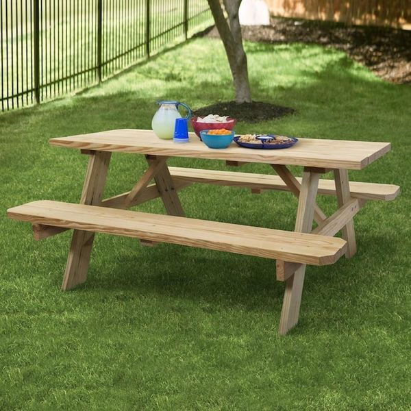 A wooden picnic table on the grass