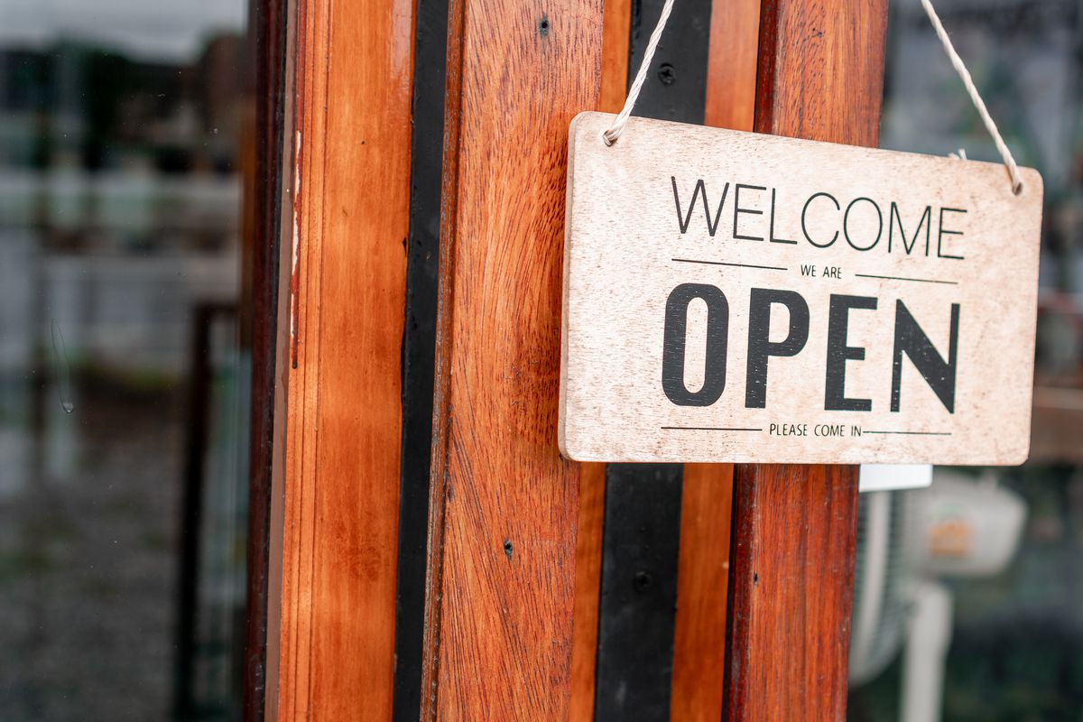 """A sign outside a wood-framed door reads """"Welcome We Are Open."""""""
