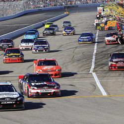 Brian Vickers edges Denny Hamlin out of the pits during the NASCAR Sprint Cup Series auto race at New Hampshire Motor Speedway, Sunday, Sept. 23, 2012, in Loudon, N.H.